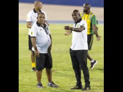 Jamaica senior women's team head coach Hue Menzies (left) in discussion with his assistant, Lorne Donaldson, after the Reggae Girlz's Concacaf Caribbean Women's Qualifier match against Antigua at the National Stadium on Saturday, August 25, 2018.