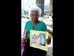 Melita Daley shows off a vintage portrait of Seaga and his family.
