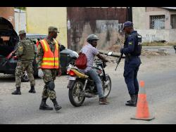 Members of the security forces conduct spot checks along a section of Waltham Park  Road in South St Andrew, which is under a state of emergency.