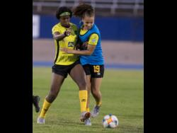 Khadija Shaw and Toriana Patterson (right) in a tussle for the ball during a Jamaica senior women's football team  training session held at the National Stadium on Monday, May 19.