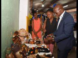 Contributed Chantal Lewis (centre) shows a pair of her sandals to Senator Pearnel Charles Jr, at the recent launch of the Palmers Cross Community Development Committee in Clarendon. Looking on is her sister, Ca-Deiva Clarke.
