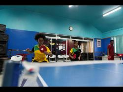 National table tennis players Gianna  (left) and Tsenaye Lewis practise at The Gleaner Company (Media) Limited's Sports Club earlier this month.