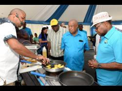 Tourism Minister Ed Bartlett (right) gets a demonstration featuring plantains at the Denbigh Agricultural, Industrial and Food Show on Sunday, August 4. Jamaica Agricultural Society President Lenworth Fulton (second right) looks on.