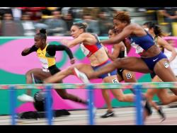 Megan Simmonds ofJamaica (left) competes in a women's 100m hurdles semi-final during the athletics at the Pan American Games in Lima, Peru, yesterday.
