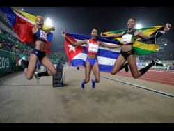 Ricketts celebrates winning a silver medal at the recently concluded Pan American Games with gold medallist Yulimar Rojas of Venezuela, and bronze medallist Liadagmis Povea of Cuba.