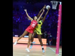 Sunshine Girls captain Jhaniele Fowler (right) outstretches England Roses goalkeeper Geva Mentor to claim the ball, before scoring a goal during their Group G match of the Vitality Netball World Cup.