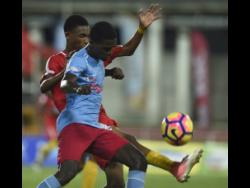 St George's  College's Konato  Campbell (right) shields  the ball from Calvin  Stephens of  Cornwall  College in a  Champions Cup  encounter last year.