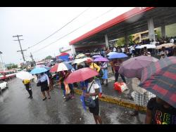 Commuters are stranded in the rain on North Odeon Avenue yesterday due to the withdrawal of services by drivers of the Jamaica Urban Transit Company.