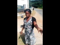 Claudette Jarrett shows the cuts and bruises she received from her son outside the Yahweh compound in St James.
