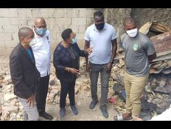 Minister of Sports Olivia Grange (third left) in discussion with Akeem Chambers (right), Reggae Boyz head coach Theodore Whitmore (second right), Jamaica Football Federation president Michael Ricketts (second left) and Mayor of Kingston Delroy Williams in Olympic Gardens yesterday. The group visited the burnt-out house of Akeem Chambers and his brother Tafari. Grange said the Government would play a big role in helping to rebuild the house.