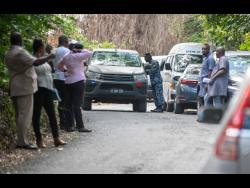 Police and military personnel at the cordoned off scene in Pear Tree River in St Thomas where three bodies, including that of a baby, were found yesterday.