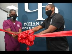 Yohan Blake, (Right) Chairman of Yohan Blake Wellness Centre and Therapist, Rupert Fearon (left), cutting the ribbon at the opening of the wellness centre official opening at 47d Old Hope Road in Kingston yesterday.