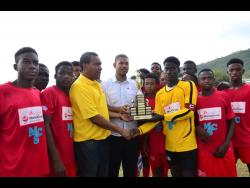 FILE Kingston and St Andrew Football Association (KSAFA) president Wayne Shaw (third left) and Brandon Chin (centre), Marketing Executive of Alliance Finance, present the trophy to Prince Daniel Smith (third right), captain of Boys Town FC after they defeated Cavalier SC 3-0 in the final of the Alliance/MoneyGram/KSAFA under 17 football tournament at Excelsior High School on Saturday, August 4, 2018.