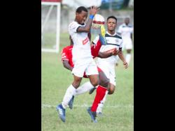 File Cavalier player Chevonne Marsh takes evasive action from a tackle by UWI'S Tejuran Williams who attempts to clear a ball while  Alex Marshall looks on in their Red Stripe Premier league encounter at the UWI Mona Bowl on December 2,2018.