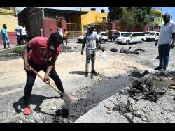 Owen Thomas (left), taxi operator, does his part to fix the roadway.