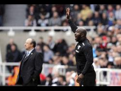 FILE West Bromwich Albion caretaker manager Darren Moore gestures, with Newcastle United manager Rafael Benitez in the background on the touchline, during the English Premier League match between Newcastle and West Bromwich at St James' Park in Newcastle, England, in April 2018.