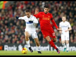 Leeds United's Kemar Roofe, left, vies for the ball with Liverpool's Emre Can during the English League Cup, quarter final  match between Liverpool and Leeds United, at Anfield, in Liverpool, England, Tuesday November 29, 2016.