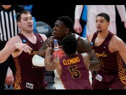 Illinois centre Kofi Cockburn (21) is defended by Loyola Chicago centre Cameron Krutwig (left)  Keith Clemons (5) and Lucas Williamson (1) during the second half of a men's college basketball game in the second round of the NCAA tournament at Bankers Life Fieldhouse in Indianapolis, yesterday.