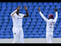 West Indies' fast bowler Jason Holder celebrates with teammate Jermaine Blackwood after he took one of his five wickets on day one of the first Test against Sri Lanka in Antigua yesterday.