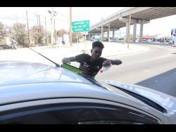 Solomon wipes the windscreen of a motorist.