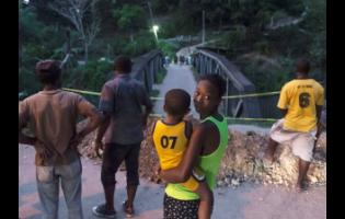 Residents look at the Long Bridge in Stony Hill, St Andrew, after it collapsed yesterday.