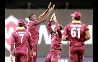 West Indies captain Jason Holder (second left) celebrates with teammates the dismissal of India's Mahendra Singh Dhoni during the third one-day international cricket match between India and West Indies in Pune, India, Saturday, October 27, 2018.