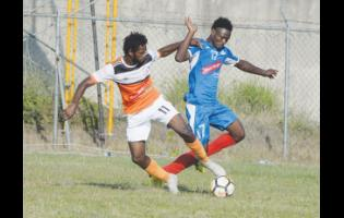 Portmore United's Andre Lewis (right) in a tussle for possession with Shevan James of Dunbeholden during their Red Stripe Premier League match at the Spanish Town Prison Oval on Wednesday. Lewis scored in Portmore's 2-0 win.