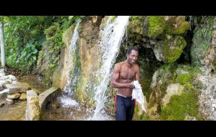 Ruel Edwards prepares to take a shower under the falls.