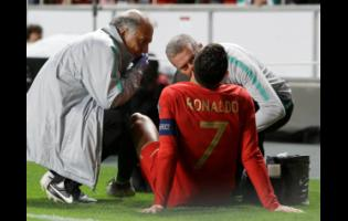 Portugal's Cristiano Ronaldo receives treatment from medical staff during the Euro 2020 group B qualifying match between Portugal and Serbia at the Luz Stadium in Lisbon, Portugal, yesterday. The match ended 1-1.