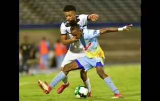 Ricardo Thomas (right) of Waterhouse fights to retain possession against Cavalier's Alex Marshall in the  Red Stripe Premier League semi-final between Waterhouse and Cavalier at the National Stadium in Kingston last Monday.