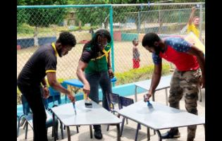 Member of Parliament for St Catherine East Central (centre) helps to paint desks at the Gregory Park Basic School.