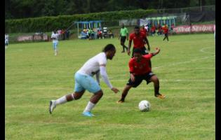 Kavarly Arnold Peter Campbell of Faulkland FC dribbles by Kymani Gayle of Downs FC in their JFF Premier League playoff match at WesPow Park on Sunday, May 26, 2019.