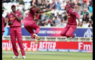 West Indies' bowler André Russel (second from right) celebrates with Darren Bravo taking the wicket of Pakistan's Haris Sohail as West Indies' captain, Jason Holder (left) smiles during a Cricket World Cup match at Trent Bridge cricket ground in Nottingham, England, last Friday.