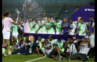 Nigerian players celebrate with bronze medals after the African Cup of Nations third-place match against Tunisia at Al Salam Stadium in Cairo, Egypt, yesterday. (AP Photo/Ariel Schalit)