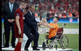 UEFA President Aleksander Ceferin and Ali Turganbekov, from Kazakhstan, right, hand the trophy to Liverpool's team captain Jordan Henderson after Liverpool won the UEFA Super Cup.