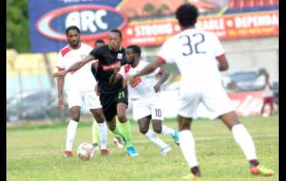 Kemar Seivwright of Molynes United FC (second left) comes under immense pressure from Arnett Gardens' Kimani Arbouine (left) and Paul Wilson  during a Red Stripe Premier League  encounter at the Drewsland Stadium on Sunday, September 22.