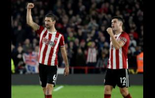 Sheffield United's Chris Basham (left) and John Egan celebrate after winning the English Premier League match between their club and Arsenal at Bramall Lane in Sheffield, England, yesterday.