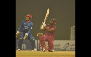 Opener Evin Lewis (right) smashes a big six in his 68 off 41 balls during the Windies 30-run win over Afghanistan in their T20 International match at the Atal Bihari Vajpayee International Stadium in Lucknow, India, yesterday.