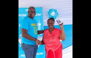 Sharon Satchel (left) of the New Life Gospel Church in Denham Town, gets a new handset from Stephen Price, Flow Jamaica's country manager, during the event.