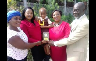 Cory-Ann Palmer (centre) shows off the medal she received for her bravery. Sharing the moment are (from left) her aunt, Stacy-Ann Brown; Shamara Brissett-Gordon, education officer and QEC-36 convenor; Judith Moore, education officer and QEC-36 co-convenor; and David Smalling, chairman of Albion Primary and Junior High School.