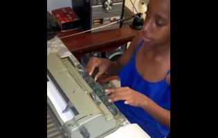 Eleven-year-old Destiny Morrison using the Braile machine.