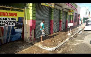 A man washes off the sidewalk where the Toyota Mark X collided with the wall of this business place.