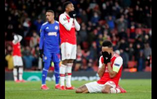 Arsenal's Pierre-Emerick Aubameyang (right) reacts after losing the Europa League round-of-32, second- leg match against Olympiakos at Emirates stadium in London, England, yesterday.