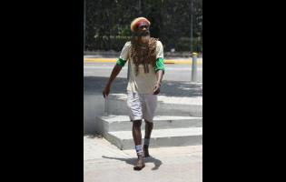 Derrick 'Black X' Robinson is known from walking around Jamaica. He is urging Jamaicans to do like him and stay home.