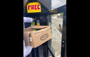 A donor places food items in the drop box.