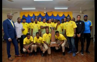 In this file photo from December 2019, team bus driver Keith Dunkley (right) poses with the Clarendon College football team during their school's celebration of their ISSA/WATA DaCosta Cup win.