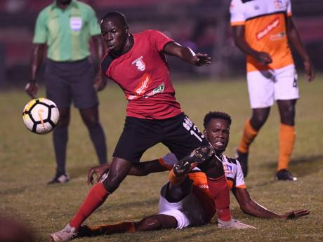 FILE Arnett Gardens player Fabian Reid (left) moves away from Dunbeholden's Clayton Pusey in their Red Stripe Premier League encounter at the Anthony Spaulding Sports Complex on Monday, December 24, 2018.