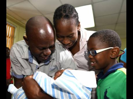 Ricardo Makyn/Chief Photo Editor Sinclair Hutton (left) holds his son Sae'breon while his partner Suzett Whyte and their other son Rudean look on lovingly. Sae'breon was reunited with his family at the Denham Town police station today, minutes after he was brought in by the Child Protection and Family Services Agency.