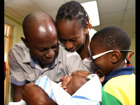 Ricardo Makyn/Chief Photo Editor Sinclair Hutton caresses his son Sae'breon alongside the child's mother, Suzett Whyte, and brother, Rudean, at the Denham Town Police Station minutes after he was returned to his family by the Child Protection and Family Services Agency last Friday.