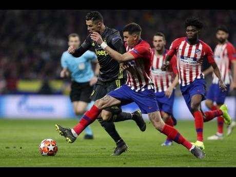 ap Atlético  Madrid defender Santiago Arias (right) puts a tackle in on Juventus forward Cristiano Ronaldo during their UEFA Champions League round of 16 first-leg match at the Wanda Metropolitano Stadium in Madrid, Spain, yesterday.